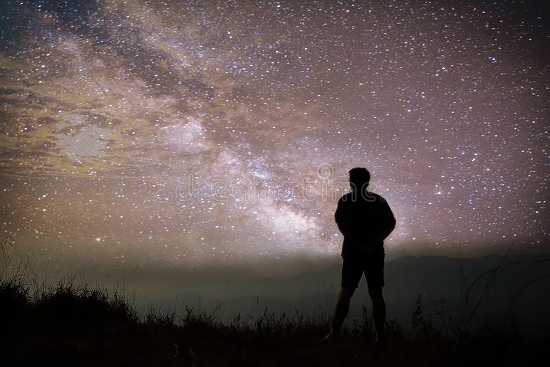 Colorful night sky with stars and silhouette of a standing man on the stone. Blue milky way with man on the mountain. stock image
