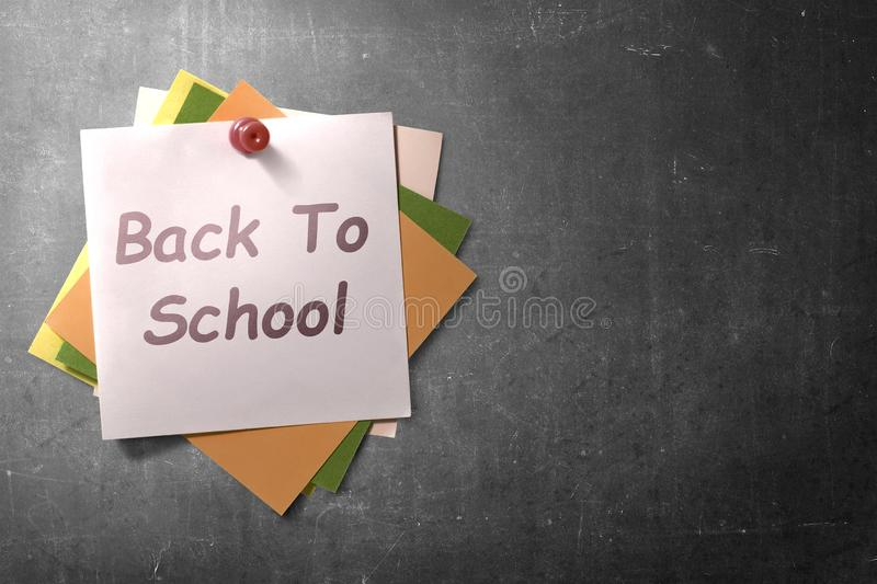 Colorful note paper in push pin with Back to School text on blackboard background royalty free stock image