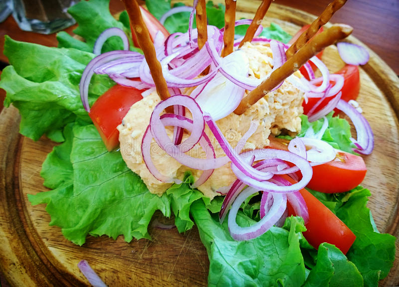 Colorful obazda, Bavarian cheese cream specialty. Obazda, Bavarian cheese cream specialty served with onion rings tomatoes, salad and salty sticks royalty free stock image