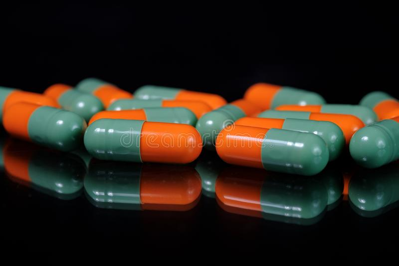 Colorful oblong pharmaceutical capsules on reflective surface, black background. Orange and green pharmaceutical pills or tablets or capsules arranged on dark royalty free stock images