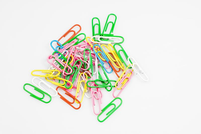 Colorful office paper clips on white ground. Office acc. Essories on a white table. White background royalty free stock photo