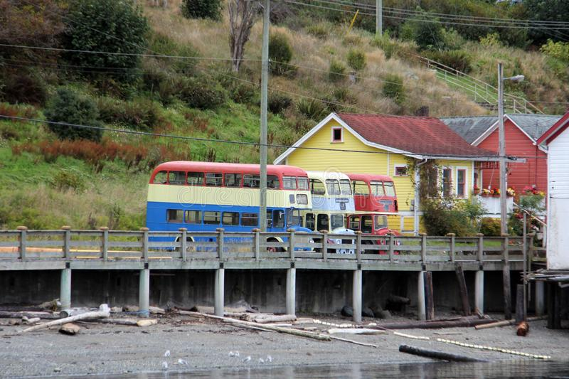Colorful old Double Decker buses and buildings Alert Bay, BC. Alert Bay is a village on Cormorant Island, in the Regional District of Mount Waddington, British royalty free stock image