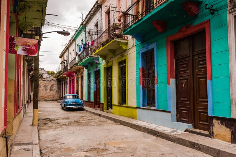 Colorful Old Havana Alley. Havana, Cuba / March 22, 2016: Brightly painted facades of Colonial era buildings with second story wrought iron balconies in an alley stock photography