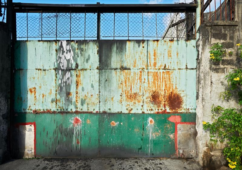 Colorful old rusty metal gate of an industrial compound royalty free stock image