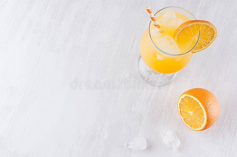 Colorful orange cool citrus cocktail with slice oranges, ice cube, straw on white modern wooden background, top view. stock photography