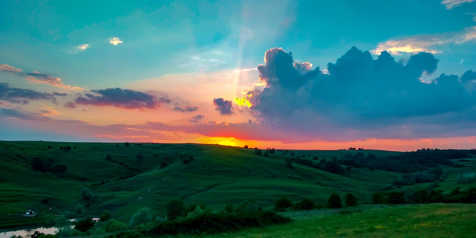 Colorful orange sunset on green hills with a calming blue sky durig a warm summer. A wonderful orange sunset on green lively hills with a blue calming sky and royalty free stock image