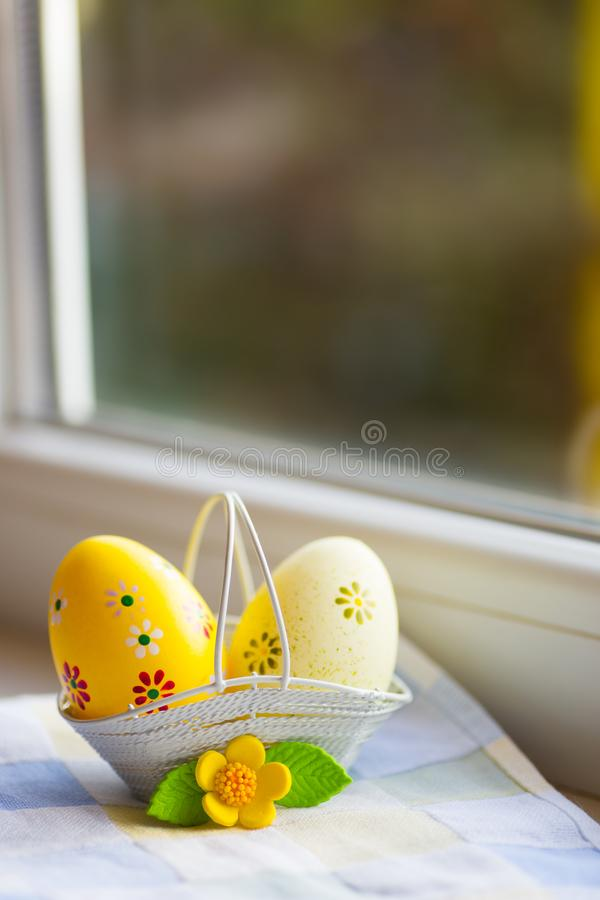 Colorful orange and yellow Easter eggs in basket with decorative flower near window in daylight stock photos