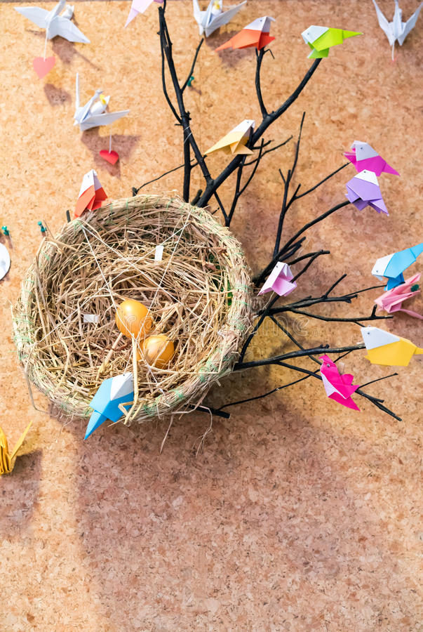 Colorful origami birds with colorful plastic pins and bird`s net. Stick with cork board for decoration stock images