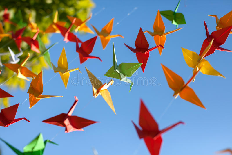 Colorful origami birds flying. Sky background. Outdoors royalty free stock images