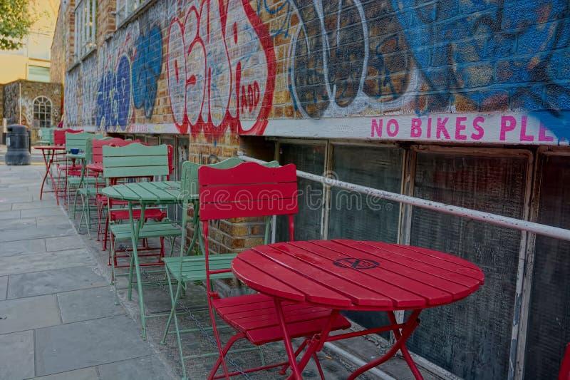 Urban street cafe, colorful Chairs & brick wall graffiti royalty free stock photos