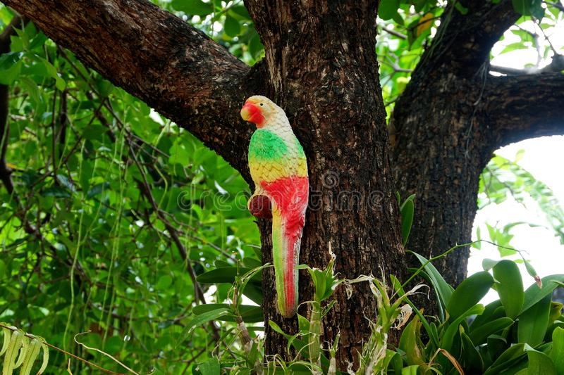 Colorful Outdoor Parrot Statue Perched on a Tree Branch royalty free stock photography