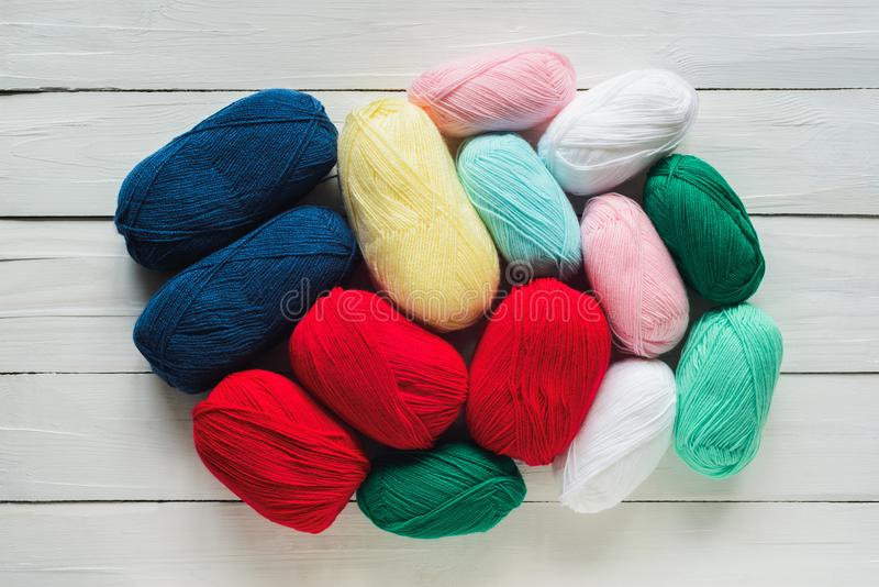 Colorful oval acrylic yarn wool thread skeins. Colorful oval acrylic yarn wool skeins in circle heap on white wooden table background, top view flat lay royalty free stock photography
