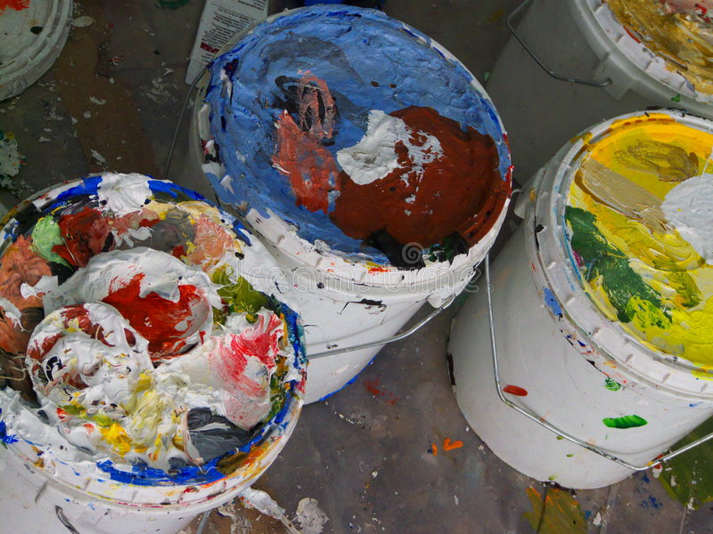 Colorful paint cans. White five gallon paint drums with paint covering stock image