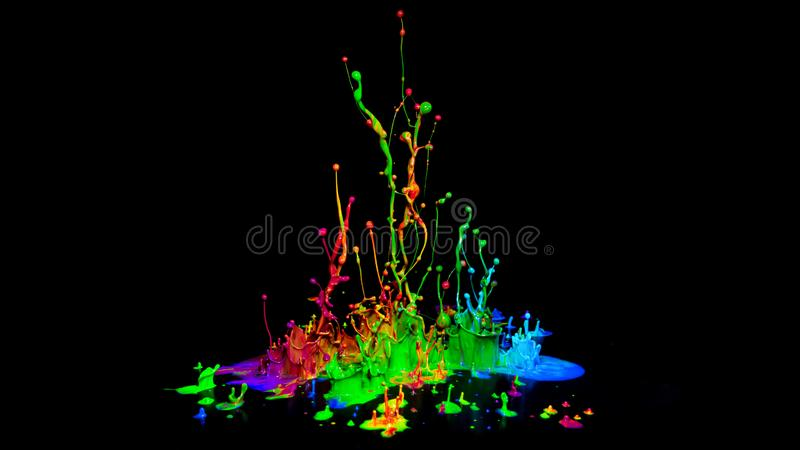 Colorful paint splashing on audio speaker isolated on black background stock images