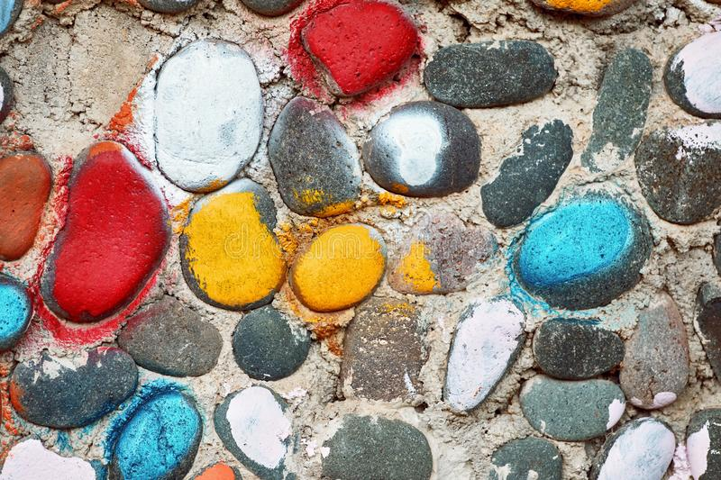 Colorful painted cobble stones on the textured surface of a pebble stone wall royalty free stock images