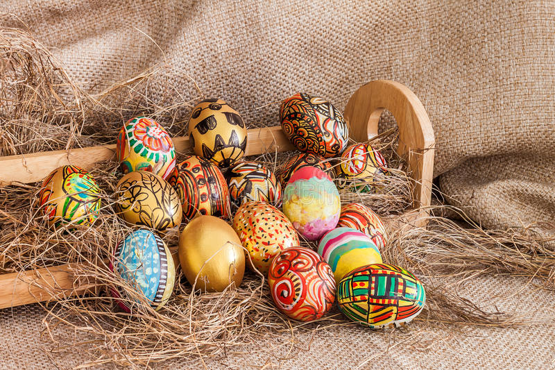 Colorful painted easter egg on hay in wooden shelf. With sack background stock images