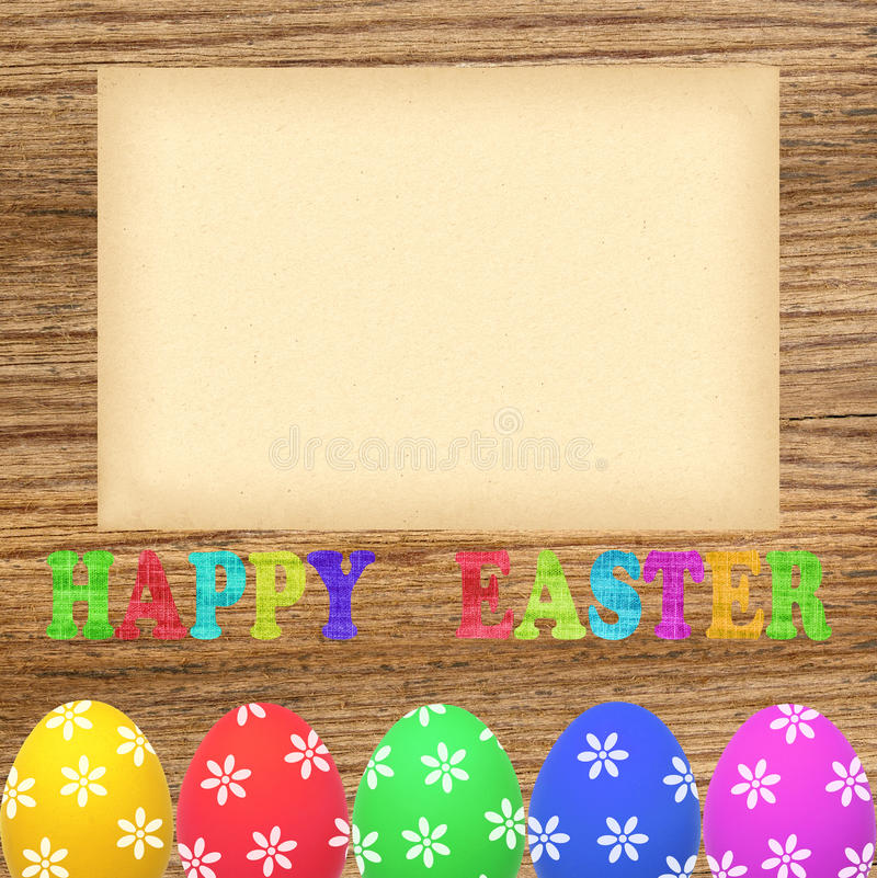 Colorful painted easter eggs and blank paper on wooden table royalty free stock images