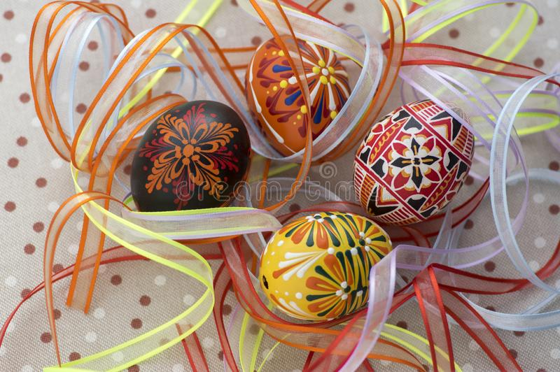 Colorful painted Easter eggs on dotted tablecloth covered with bright colorful ribbons, traditional beautiful Easter still life royalty free stock images