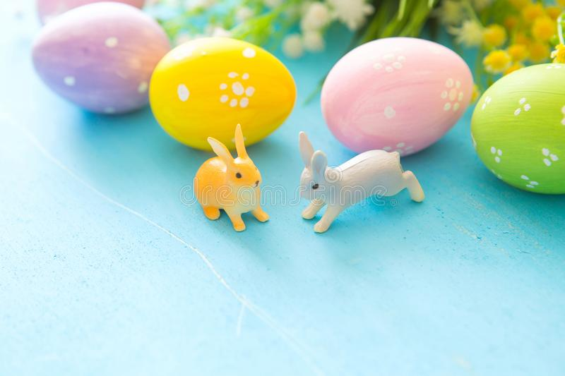Colorful painted Easter eggs with flowers on blue wooden background stock images