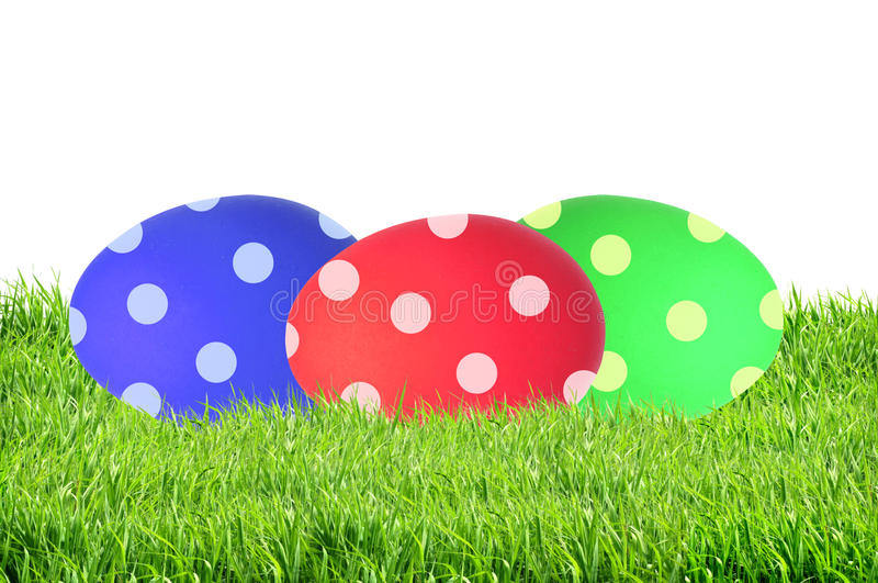 Colorful Painted Easter Eggs in green grass isolated on white stock photo
