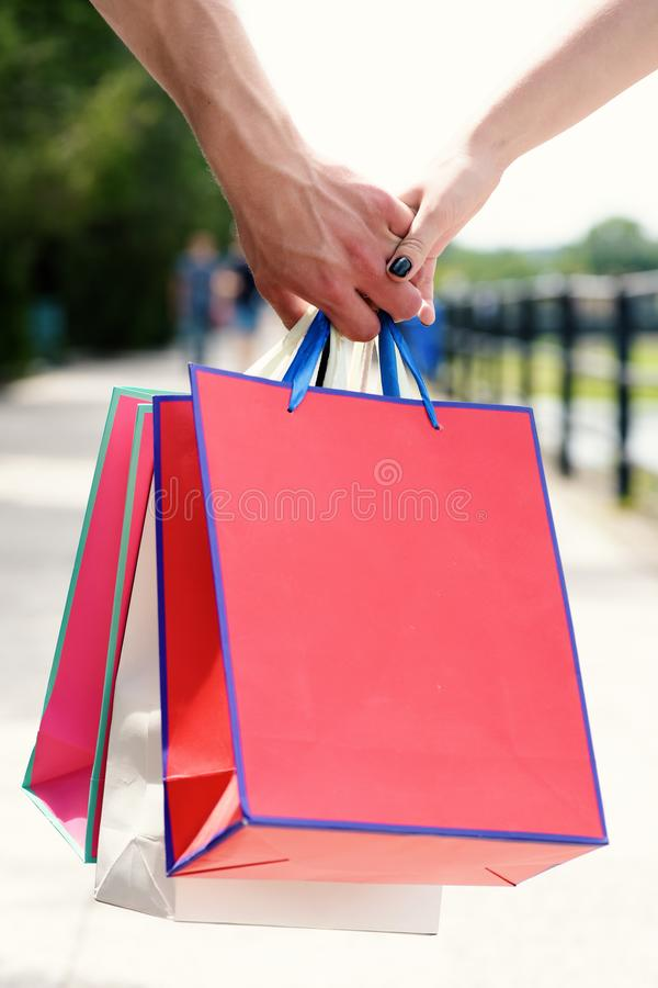 Colorful paper bags in hands of couple. Shopping bags. In male and female hands. Bags with gifts, presents, items with nature on background, defocused. Shopping stock image