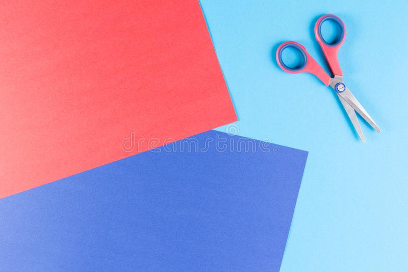 Colorful paper with child`s scissors. Colorful paper with scissors on blue background stock images
