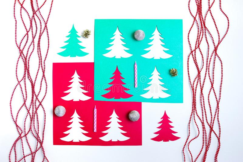 Colorful paper Christmas trees with red garlands, thin candles, gold cones and balls on white background. Design papercraft card stock image