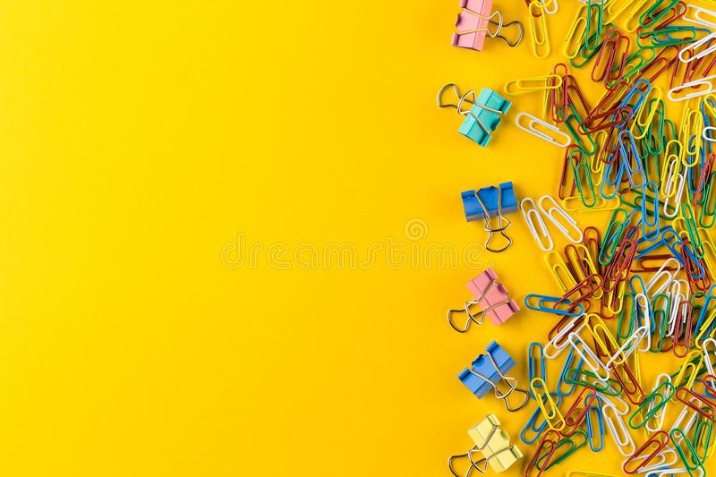 Colorful paper clips and binder clips on yellow background. Creative flat lay back to school concept on bright yellow paper background with copy space stock photos