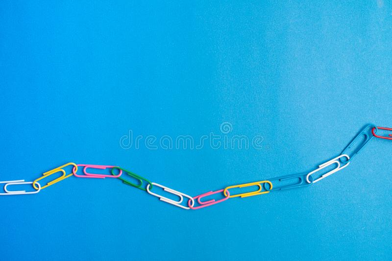Colorful paper clips on blue background. Back to school. Various color wire plugs are one type of office material. Copyspace. Multicolor paper clips on blue stock photos