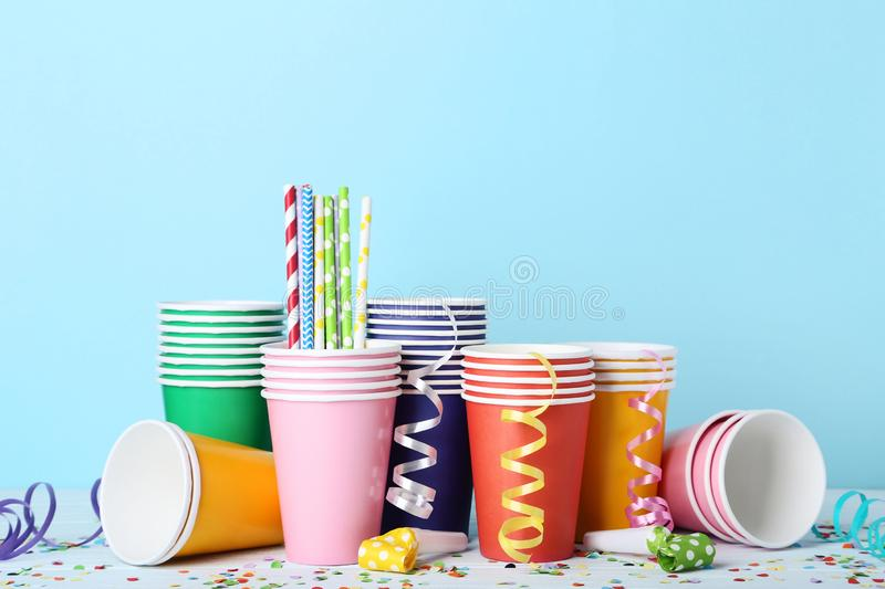 Paper cups with straws and confetti. Colorful paper cups with straws and confetti on blue background royalty free stock photography