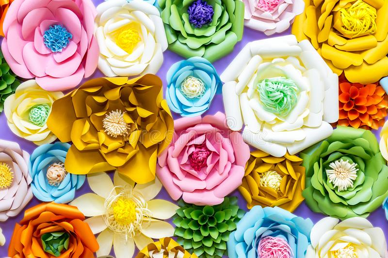 Colorful paper flowers on wall. Handmade artificial floral decoration. Spring abstract beautiful background and texture stock photo