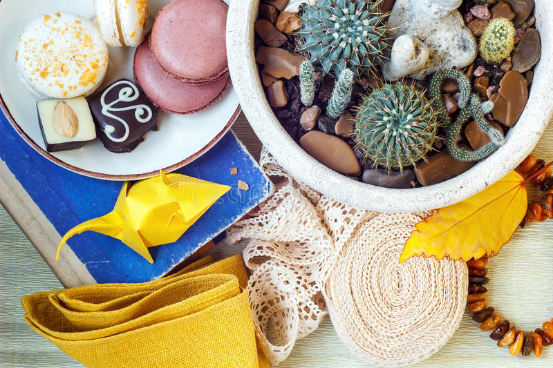 Colorful paper origami, colored macaroons, vintage lace ribbon, amber, flower in a pot, book and napkin on the table. Still life. royalty free stock image