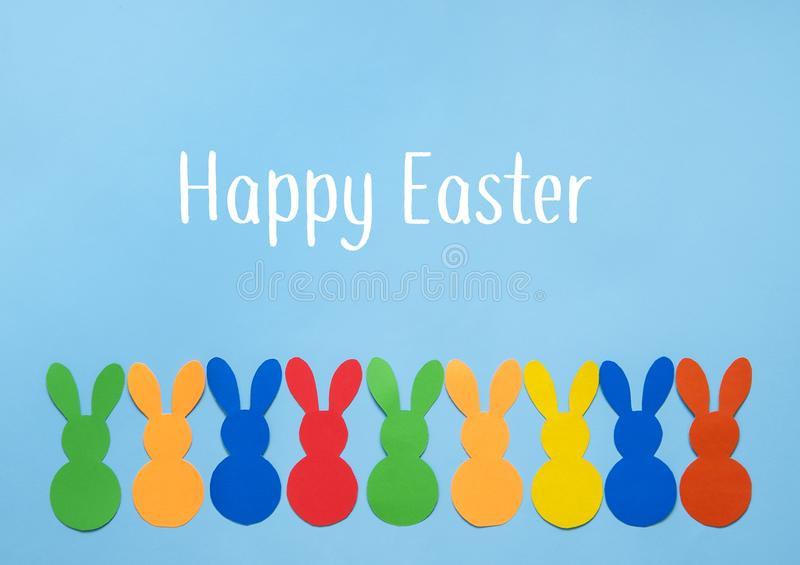 Colorful paper`s rabbits on blue background. Happy Easter royalty free stock photo