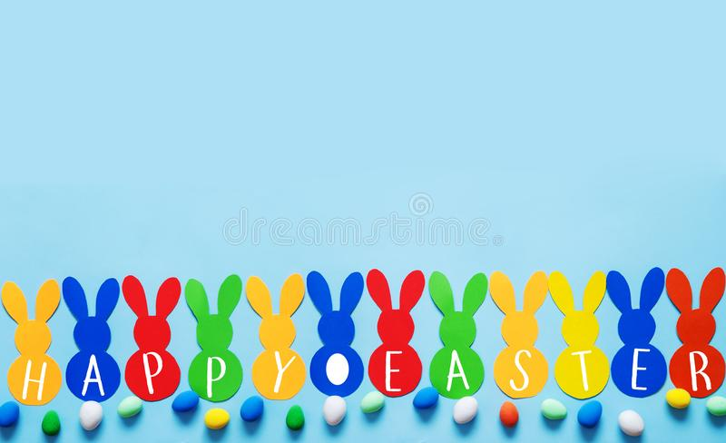 Colorful paper`s rabbits with an eggs on blue background. Colorful paper`s rabbits on blue background. Happy Easter stock photography