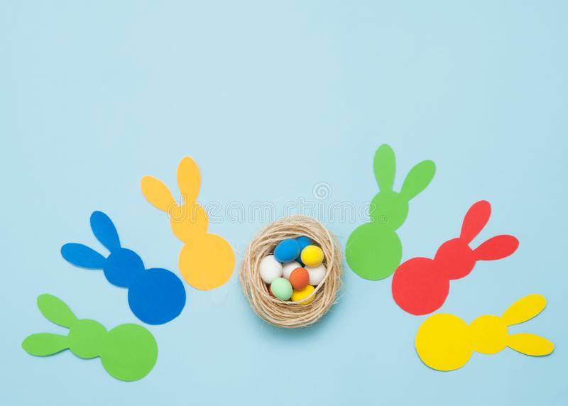Colorful paper`s rabbits with an eggs on blue background. Happy Easter royalty free stock photo