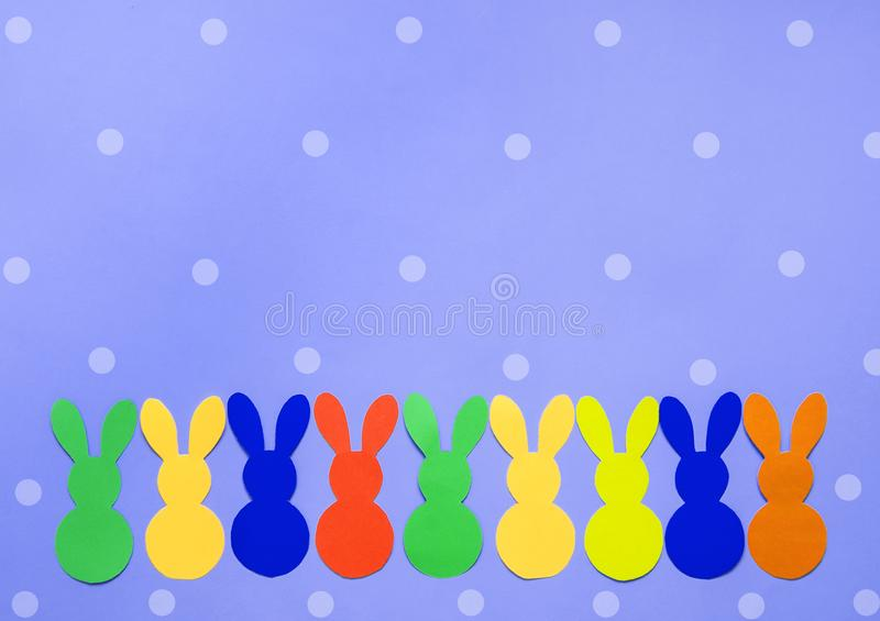 Colorful paper`s rabbits on purple background. Colorful paper`s rabbits on purle background. Happy Easter stock images