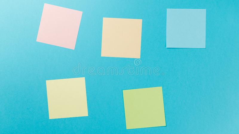 Colorful paper stickers on blue background royalty free stock photo