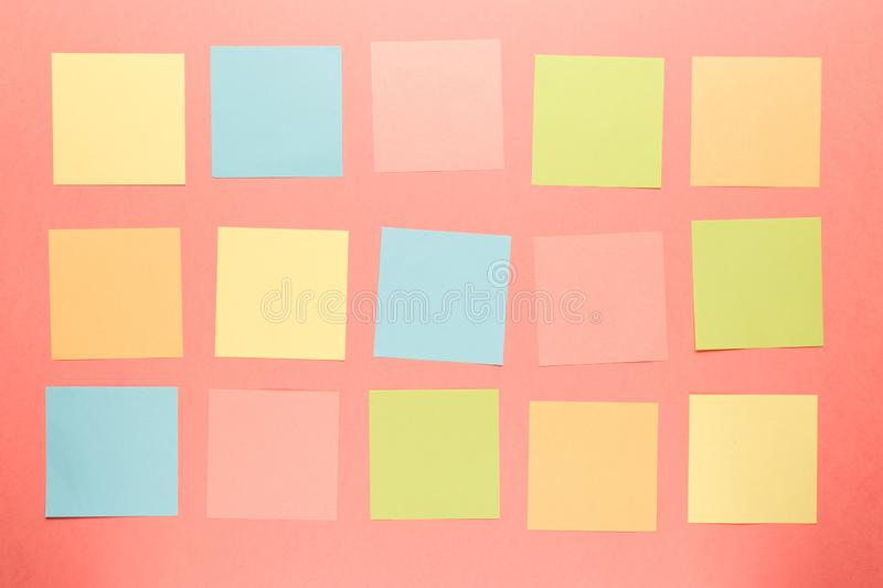 Colorful paper stickers on coral background stock photo