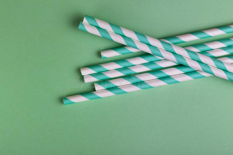 Colorful paper straws on bright green background. Event and party supplies. stock photo