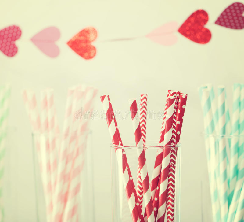 Colorful paper straws with a garland of hearts stock photos