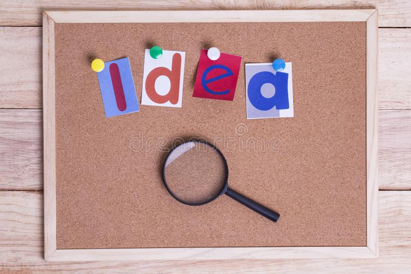 Colorful paper word IDEA with Magnifying glass on the cork board. On table . Idea Concept stock image