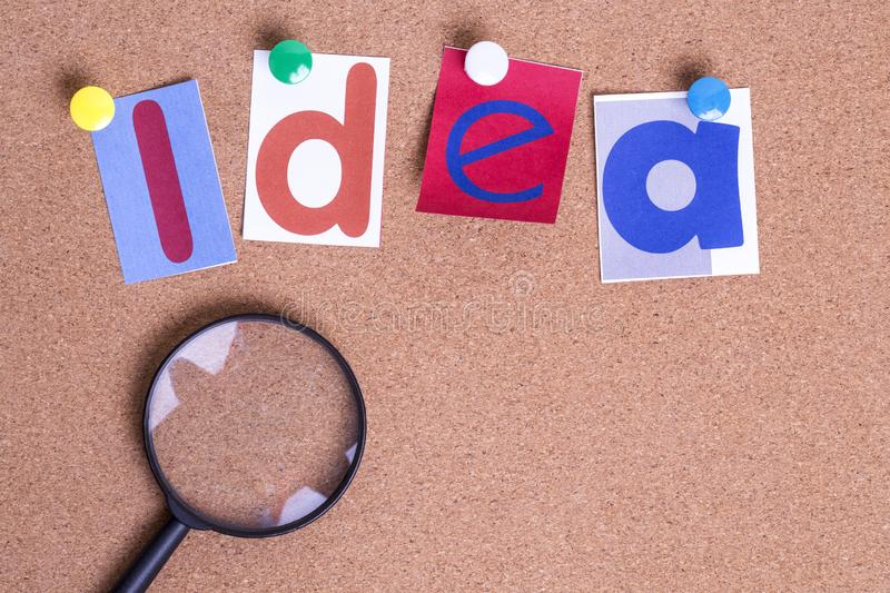Colorful paper word IDEA with Magnifying glass on the cork board. On table . Idea Concept royalty free stock photo