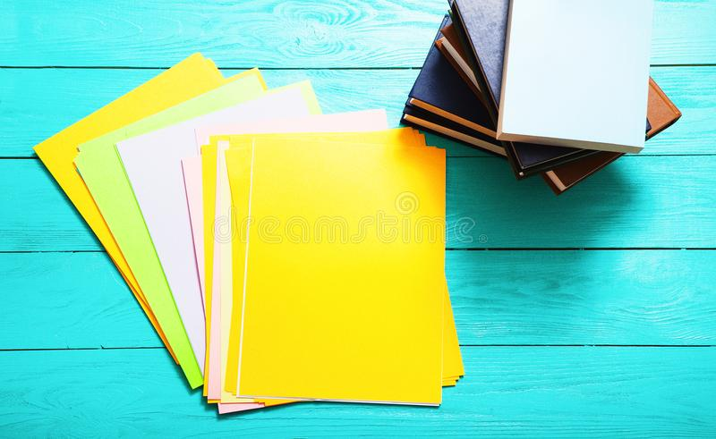 Colorful papers with copy space and many books on blue wooden table. Top view stock images