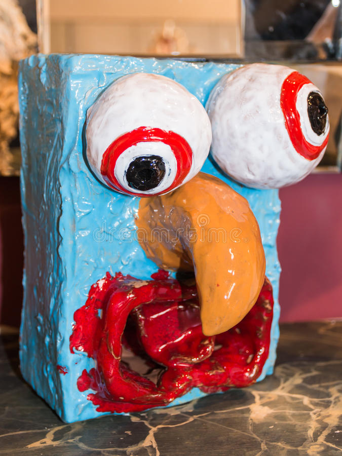 Colorful papier-mache sculpture face with orange beak. Wonky, cross-eyed and goofy art object stock image
