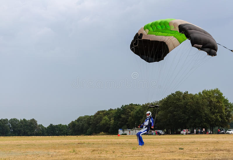 Colorful parachute landing as storm is coming stock images