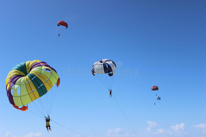 Colorful parachute landing on stormy sky. stock photo