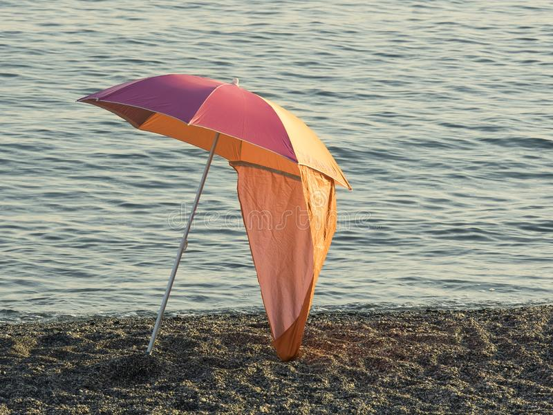Colorful parasol beach umbrella on a pebble beach at sunset stock photos