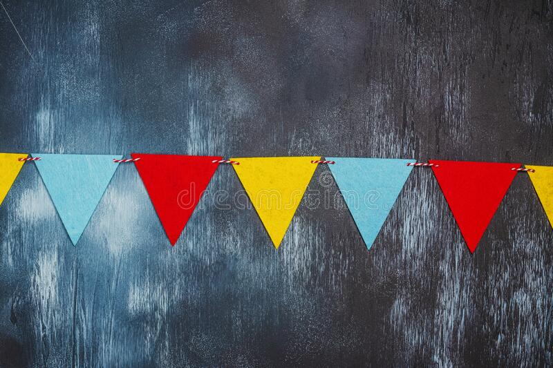 Colorful party flag garland. Over blue stone wall. Copy space royalty free stock photos
