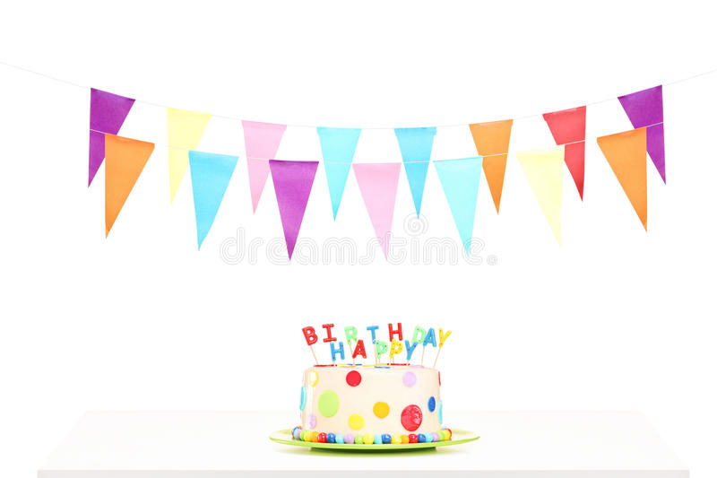 Colorful party flags and a birthday cake. Isolated against white background royalty free stock images