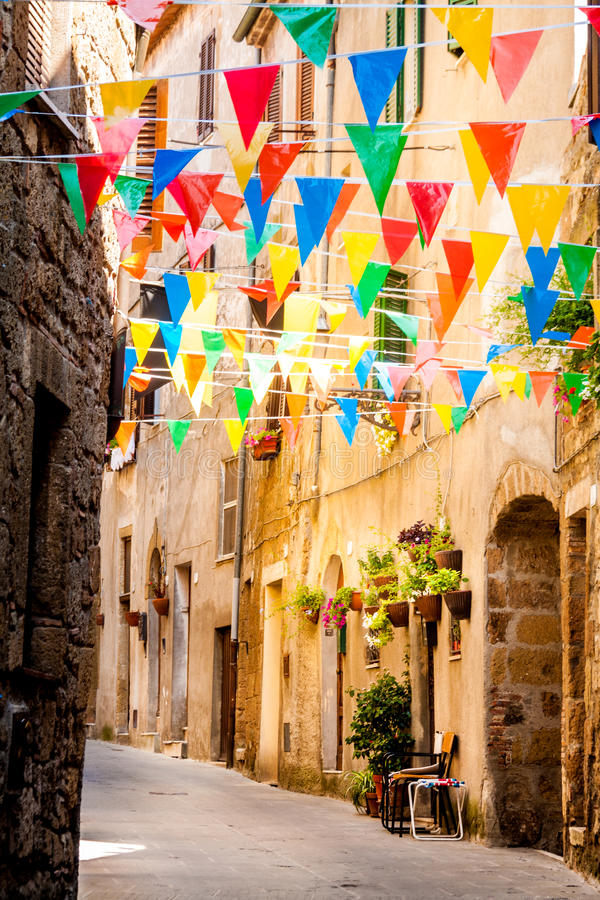 Colorful Party flags wave in a little alley. During a village festival in Pitigliano, Italy stock photography